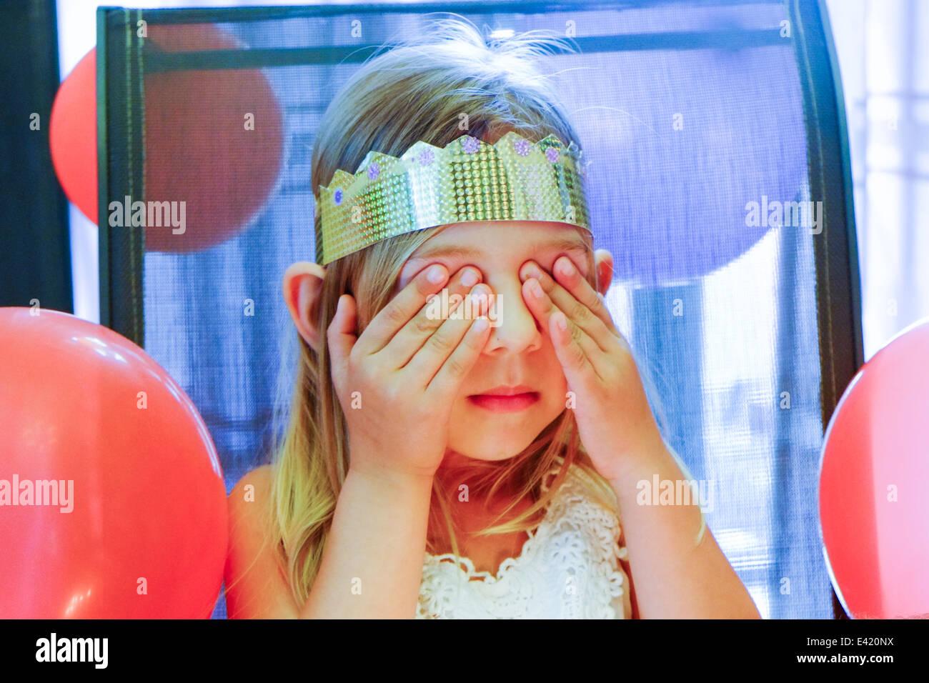 La ragazza con gli occhi chiusi rendendo desiderio di compleanno Immagini Stock