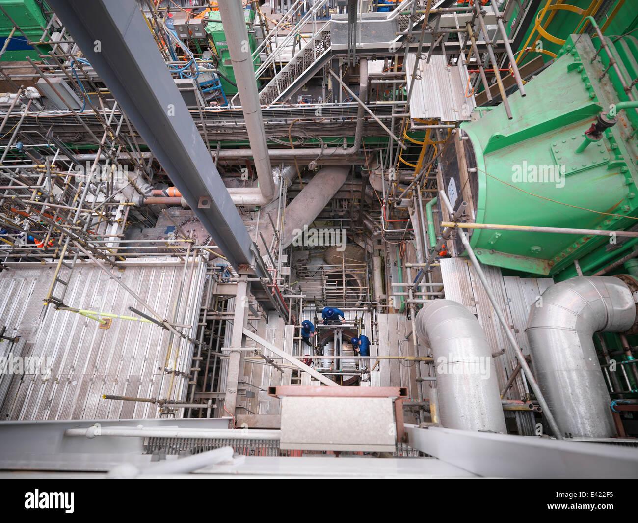 Gli ingegneri che lavorano nel profondo delle attrezzature durante power station interruzione, ad alto angolo di Immagini Stock