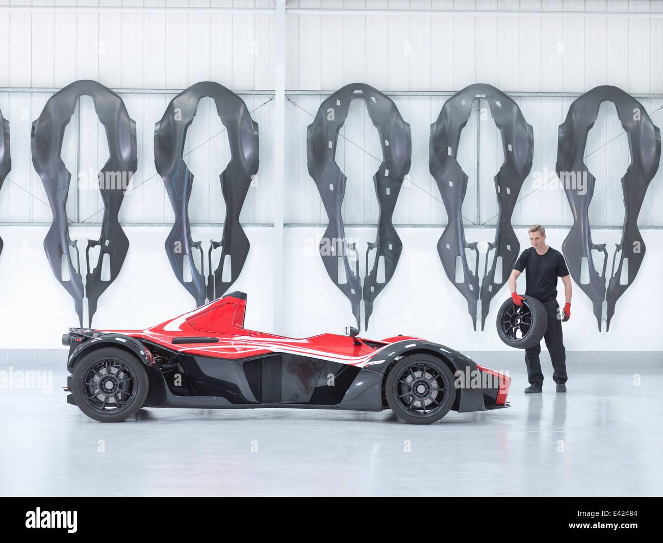 Ingegnere della ruota portante a supercar in fabbrica con fibra di carbonio auto gusci del corpo appeso alla parete Foto Stock