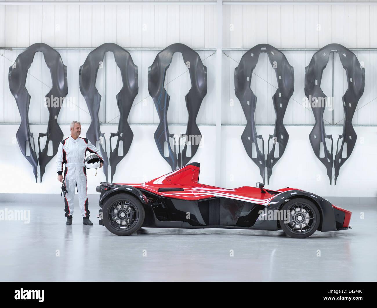 Racing driver con supercar in fabbrica con fibra di carbonio auto gusci del corpo appeso alla parete Foto Stock