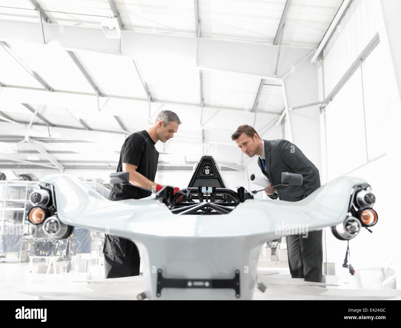 Ingegnere e designer automobilistico ispezione in parte costruito supercar in fabbrica di automobili Immagini Stock