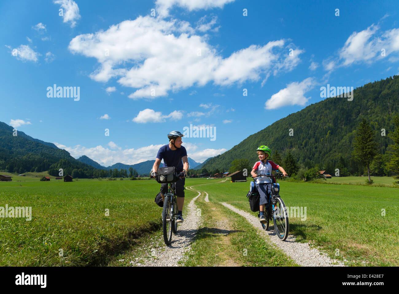 Padre e figlio in bicicletta attraverso Jachenau, Baviera, Germania Immagini Stock