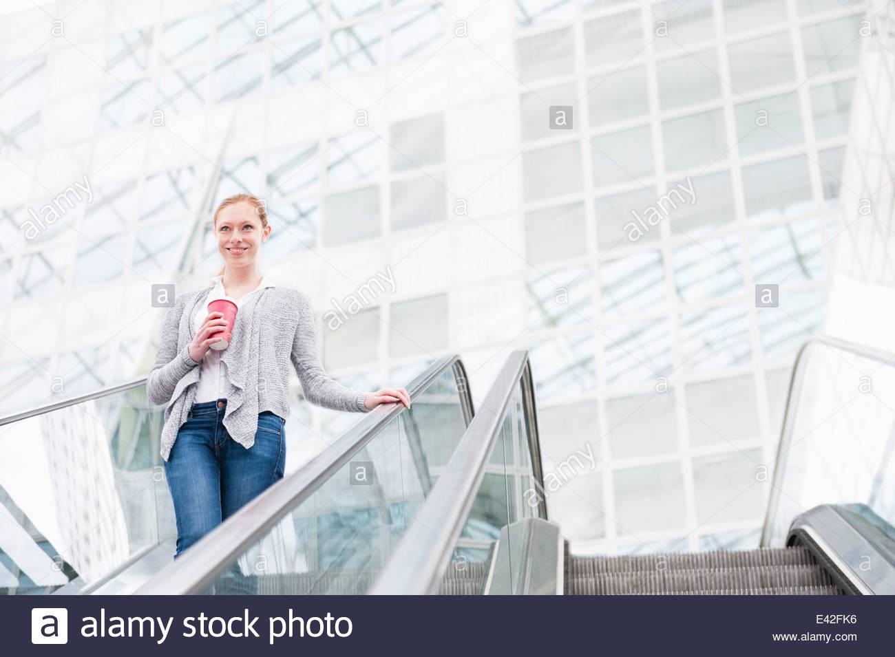 Giovane donna si sta spostando verso il basso escalator con caffè da asporto Immagini Stock