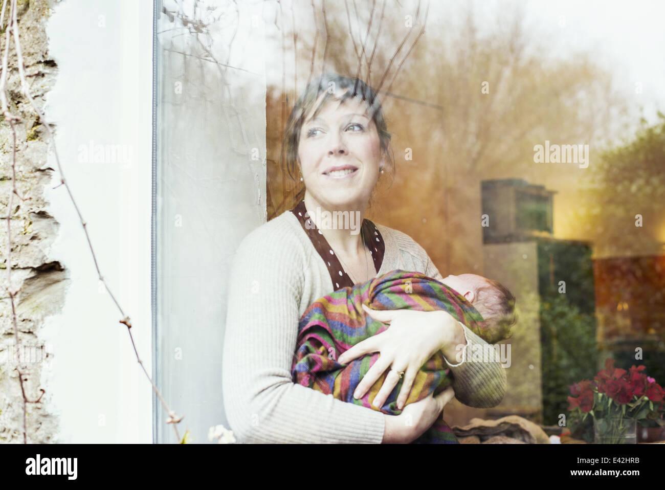 Madre con bambino guardando fuori della finestra Immagini Stock