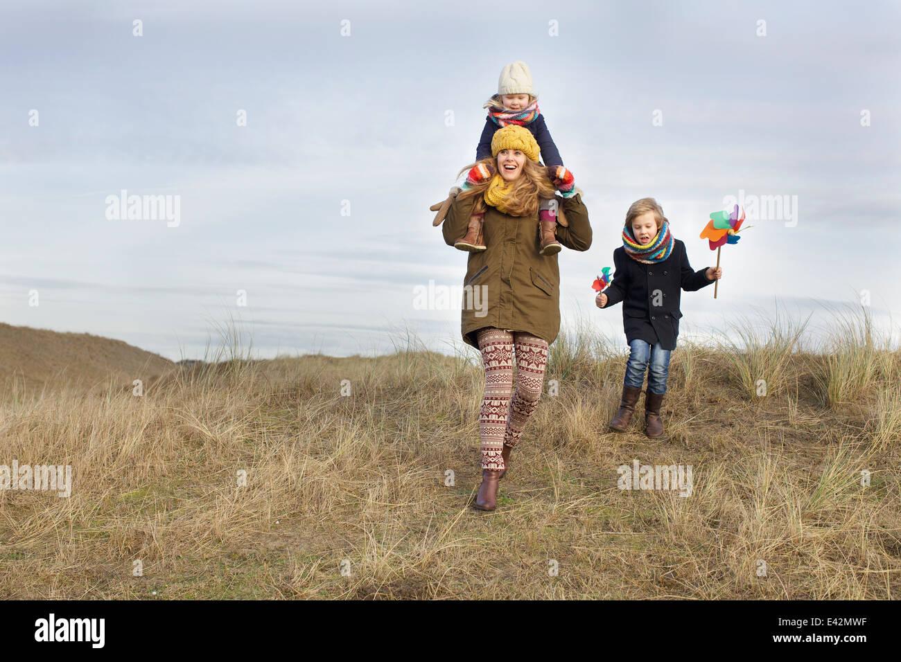 Sorridente metà donna adulta con la figlia e il figlio a costa Immagini Stock