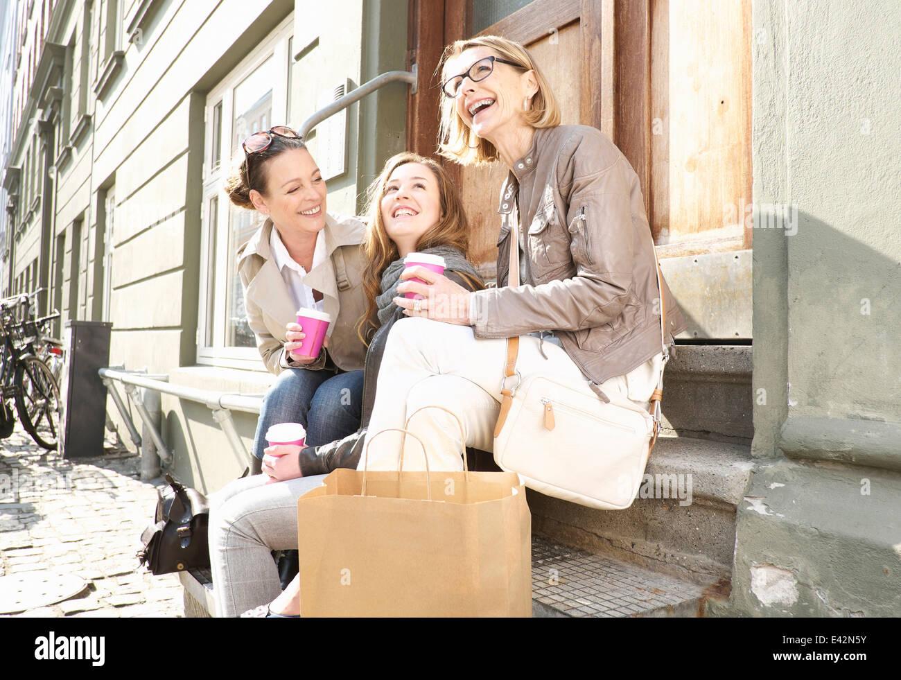 Tre femmine di generazione di bere il caffè da asporto su strada Immagini Stock