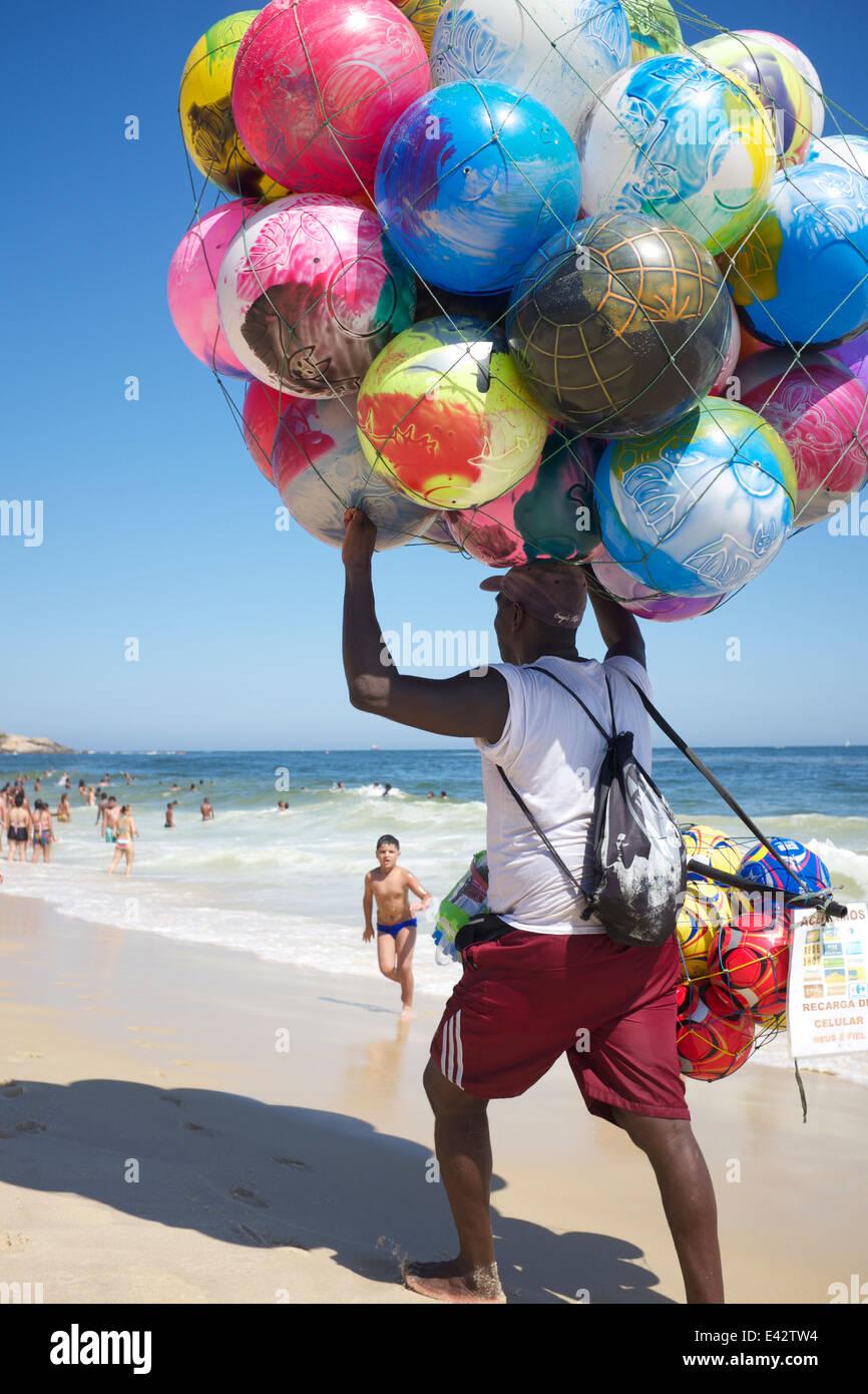 RIO DE JANEIRO, Brasile - 20 gennaio 2014: Spiaggia venditore a vendere pittoresca spiaggia di sfere porta la sua Immagini Stock