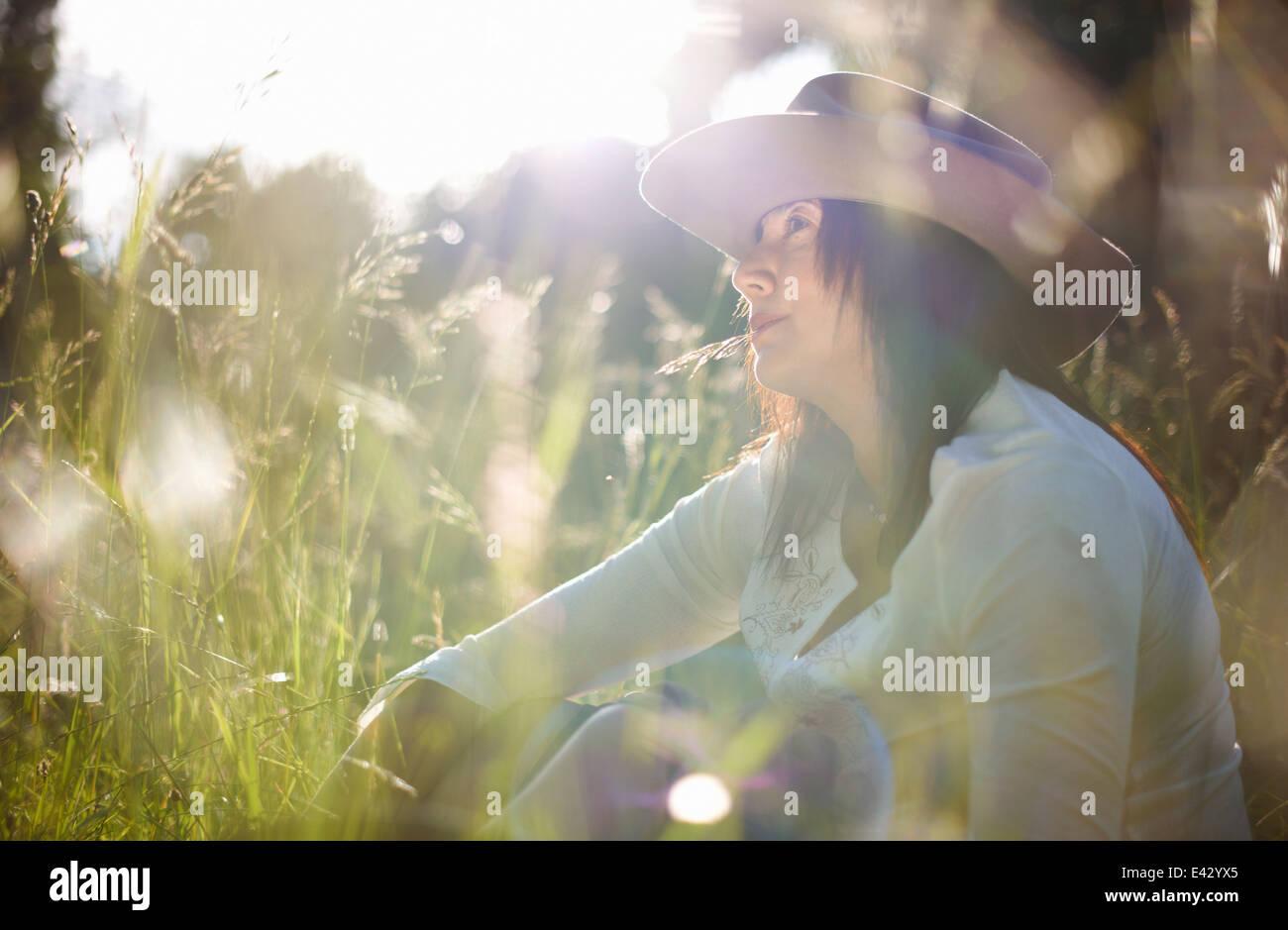 Donna matura nel cappello da cowboy con lama di erba nella sua bocca Immagini Stock
