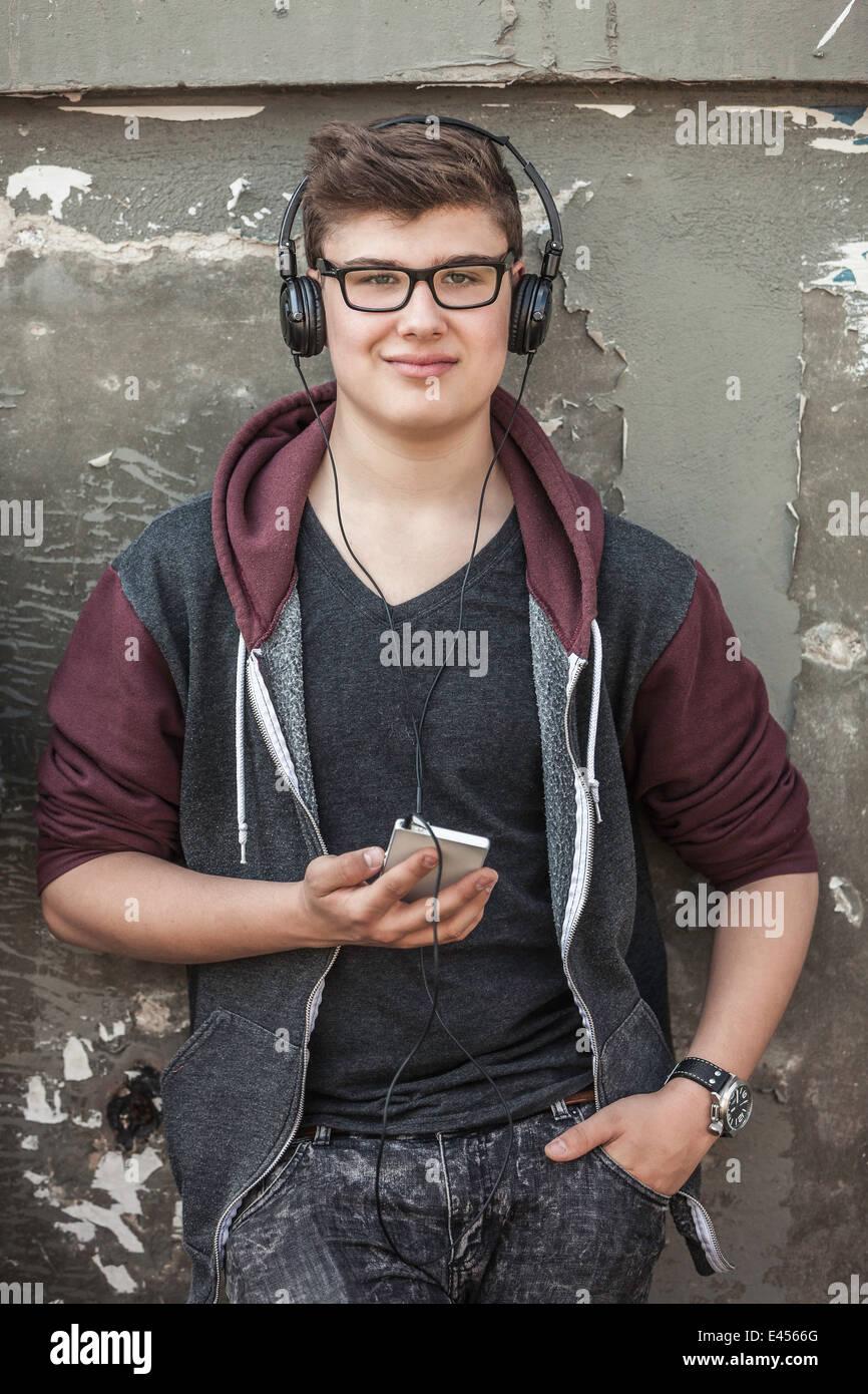 Ragazzo adolescente con le cuffie e lo smartphone Immagini Stock