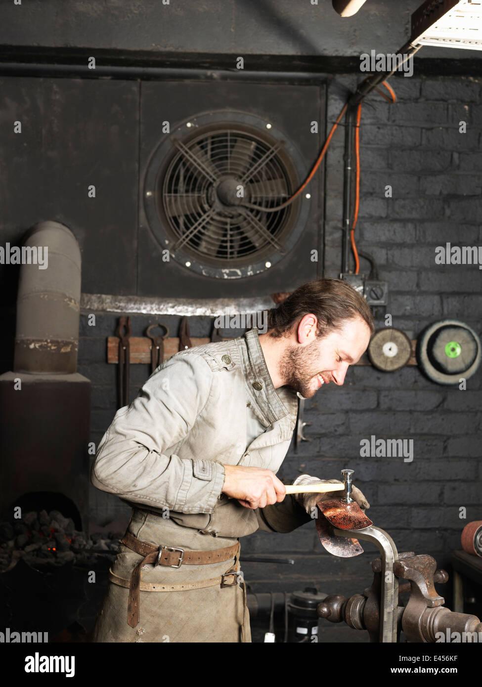 Fabbro martellare il rame in officina Immagini Stock