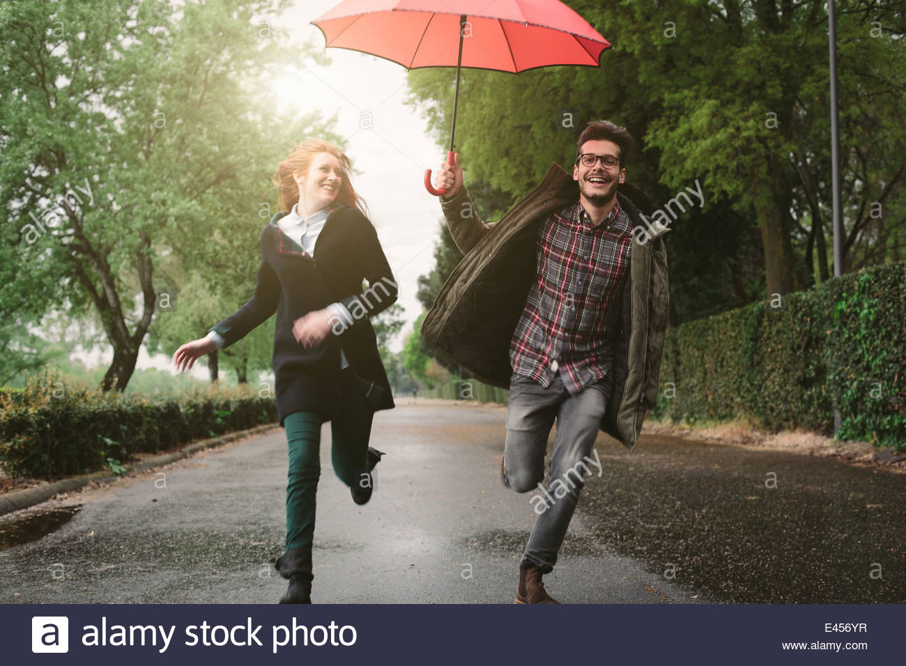 Matura in esecuzione nel parco sotto ombrellone Immagini Stock