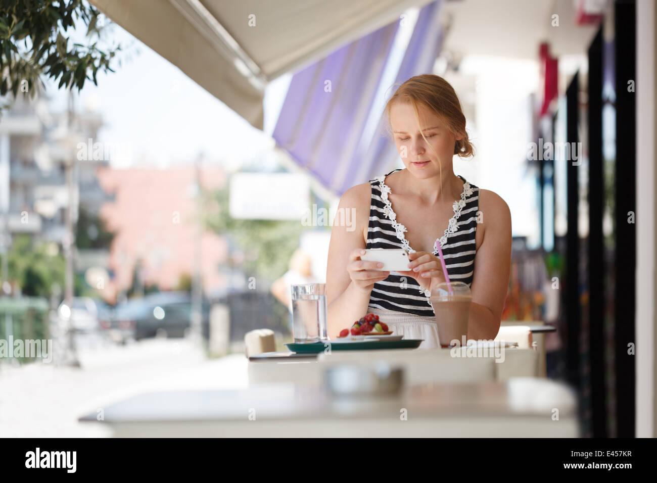 Donna con telefono in outdoor cafe Immagini Stock