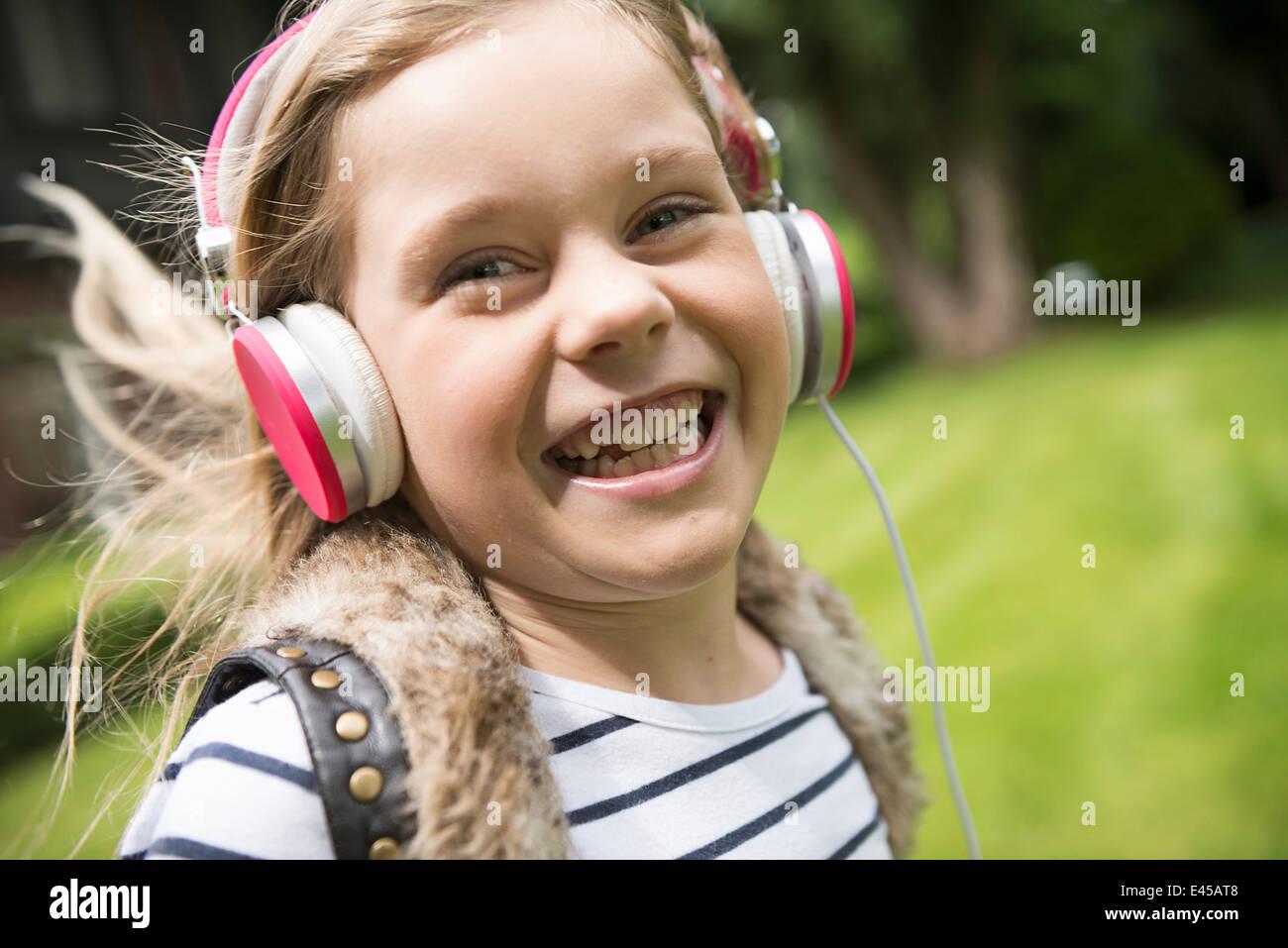 Ragazza ascoltando musica sulle cuffie Immagini Stock