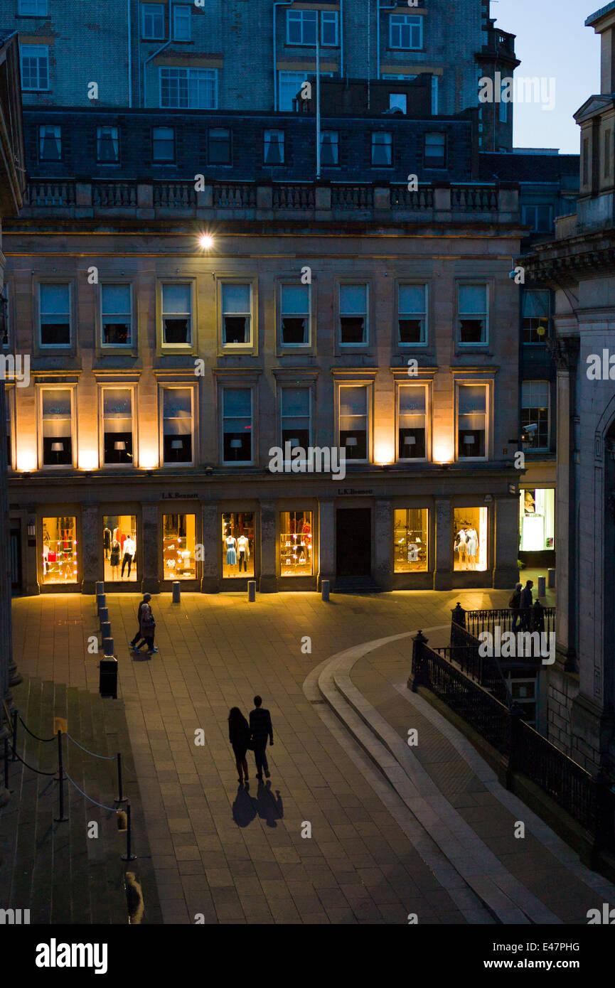 Giovane tenendo le mani e facendo una passeggiata notturna nel Royal Exchange Square nel centro cittadino di Glasgow. Immagini Stock