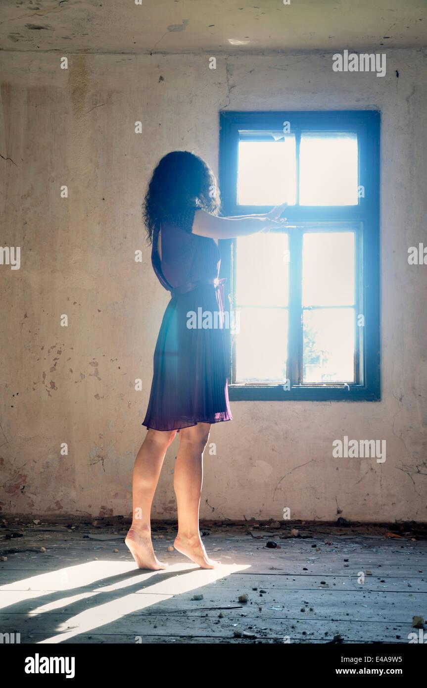 Giovane donna in piedi dalla finestra per raggiungere la luce Immagini Stock