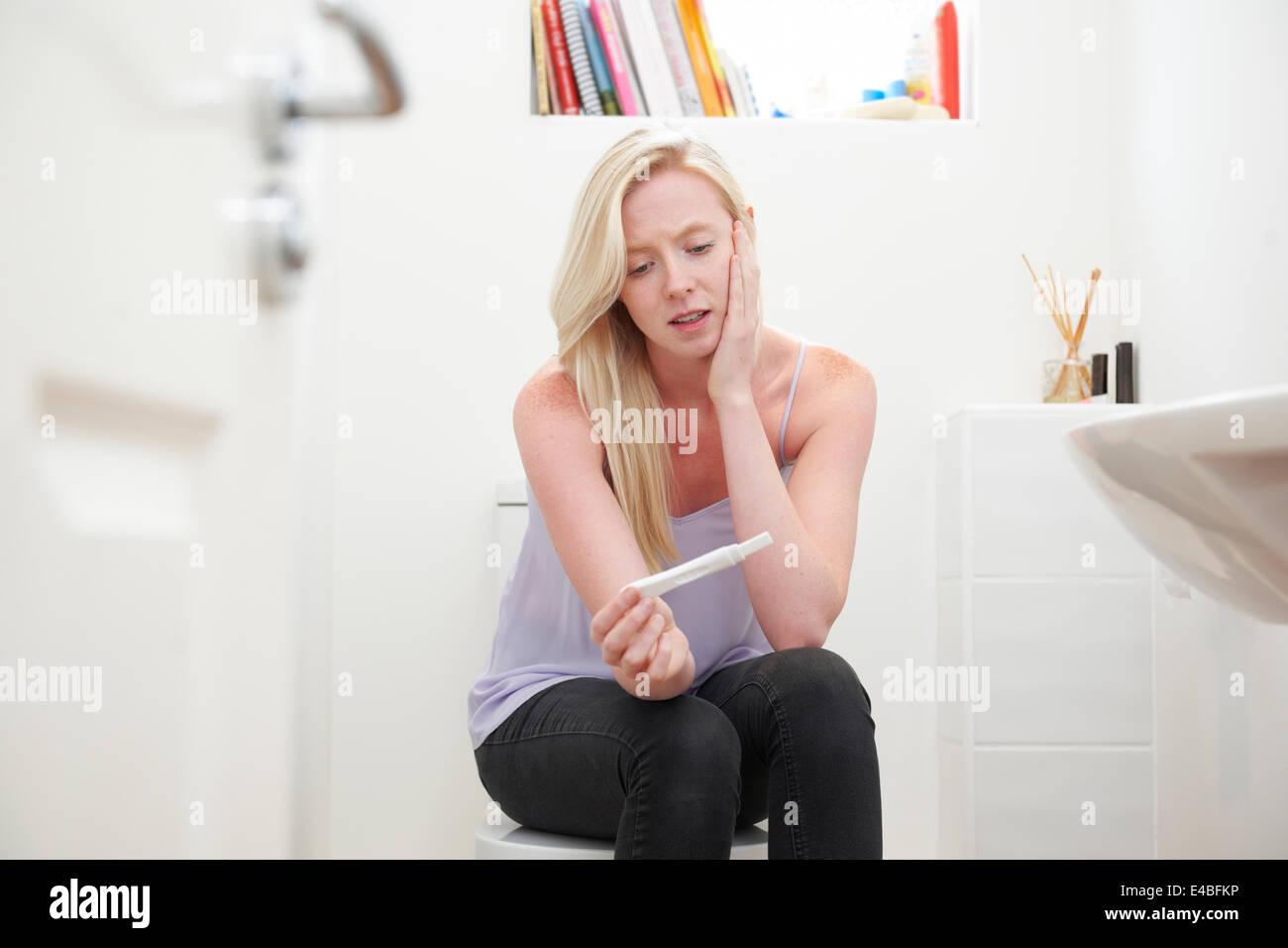 Preoccupato ragazza adolescente seduto in bagno con test di gravidanza Foto Stock