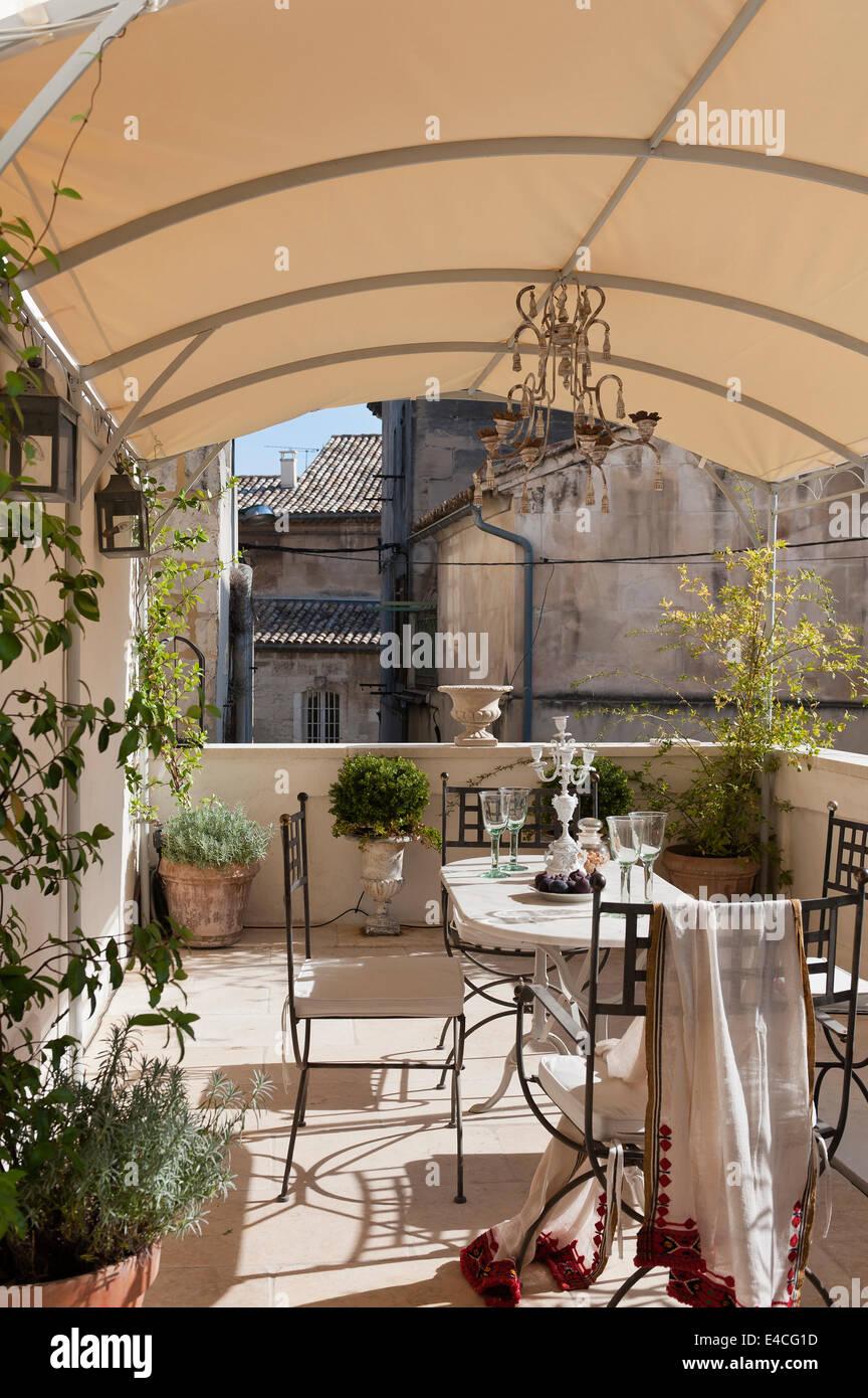 Ferro da stiro mobili da giardino sulla terrazza con tettoia e piante in vaso Immagini Stock