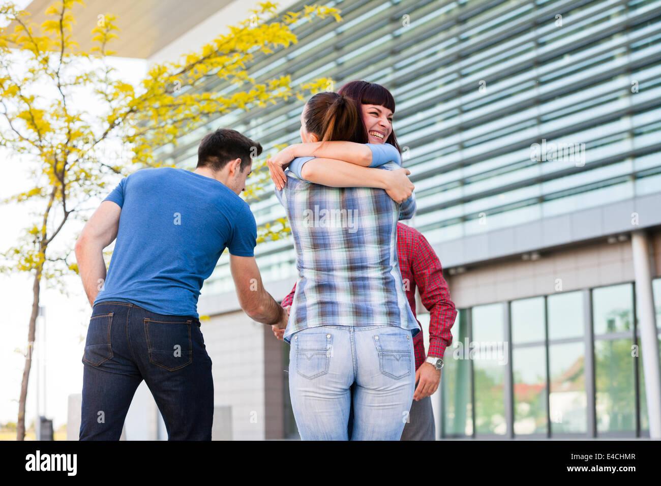 Gli amici che abbraccia e stringe la mano all'aperto, osijek, Croazia Immagini Stock