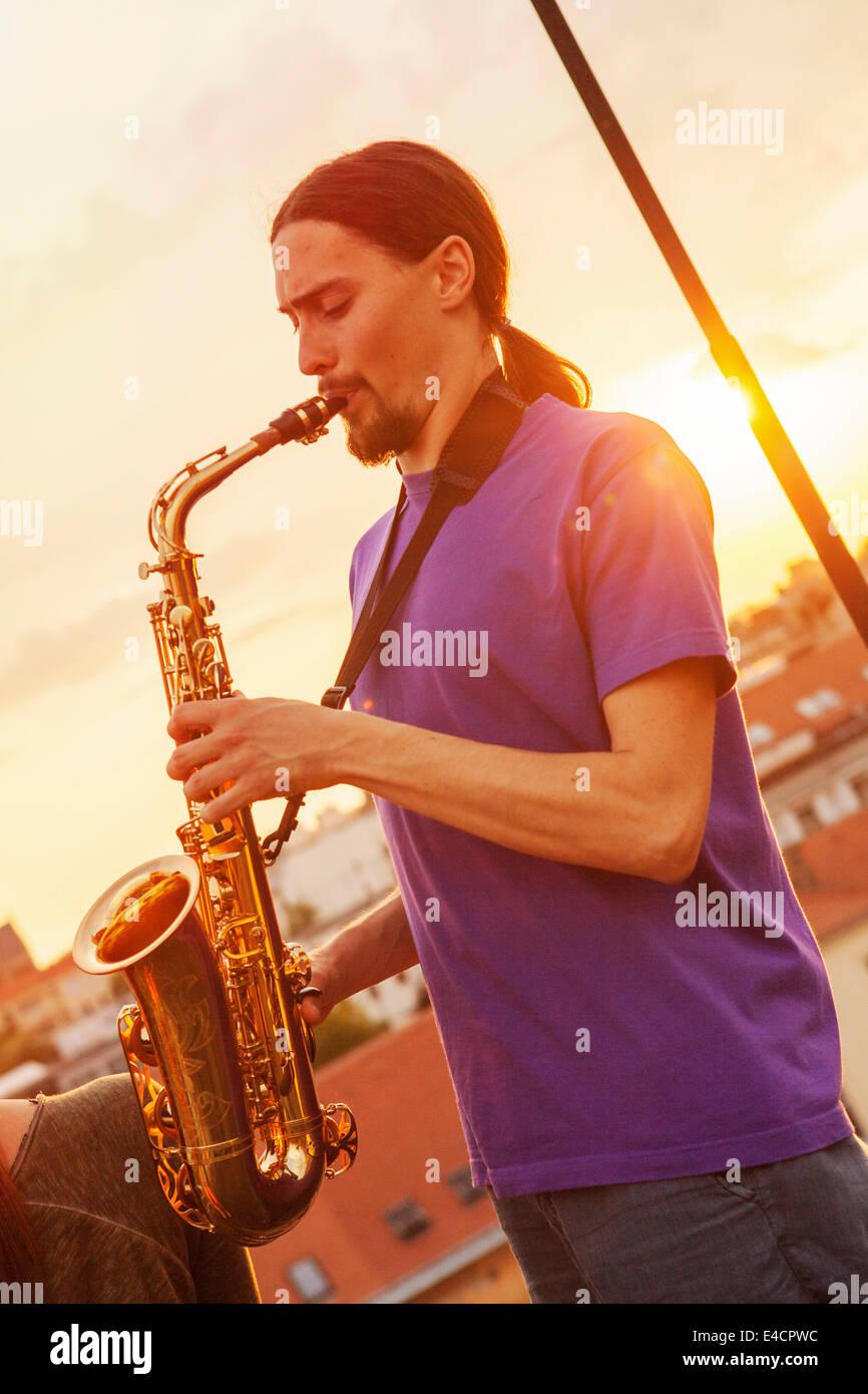 Giovane uomo suonare il sassofono al tramonto, osijek, Croazia Immagini Stock