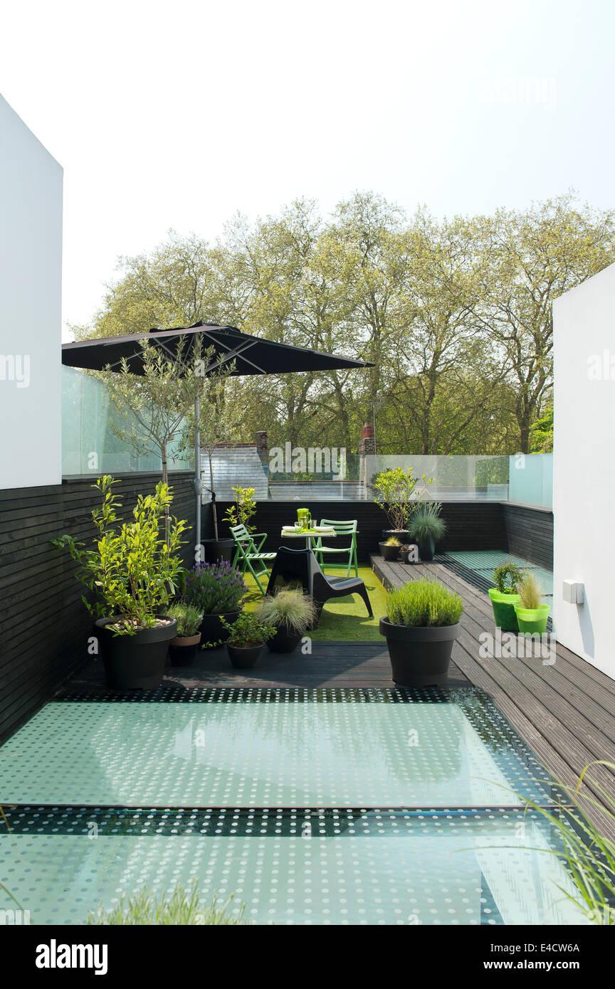 Mobili da esterno e di piante in vaso sul moderno con terrazza sul tetto Immagini Stock