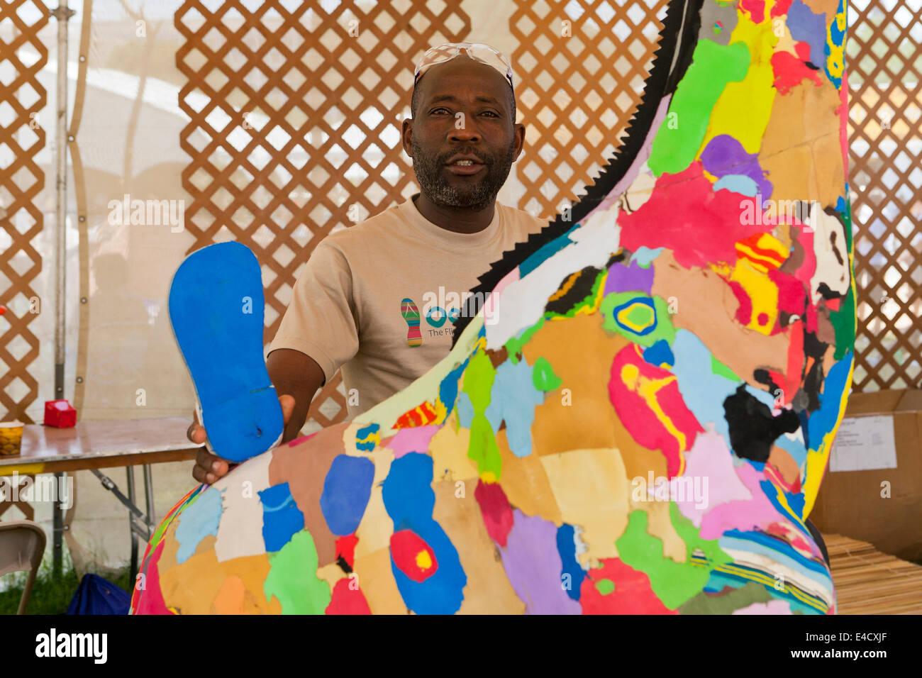 Artista keniota che utilizza lavato fino flip-flop sulla costa est africana per rendere le sculture di animali Immagini Stock