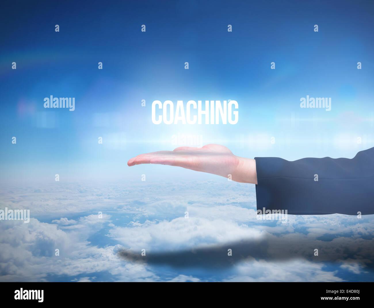 Mano Businesswomans presentando la parola coaching Immagini Stock