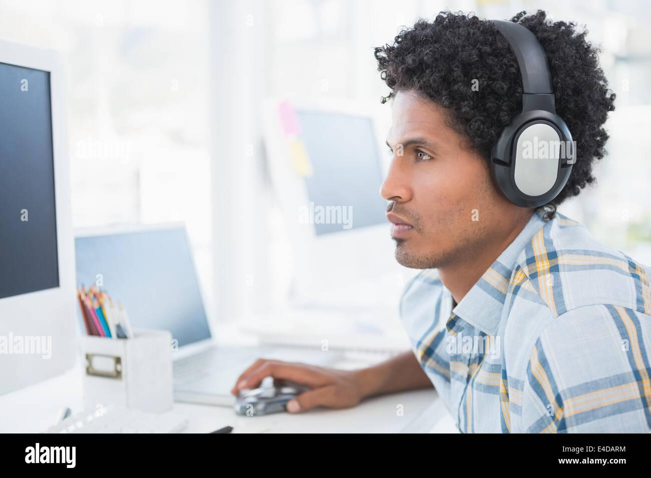 I giovani designer ascoltando la musica come lui lavora Immagini Stock