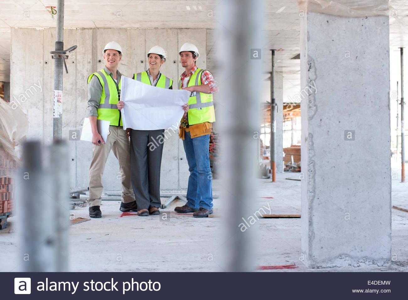 Lavoratori edili guardando blueprint sul sito in costruzione Immagini Stock