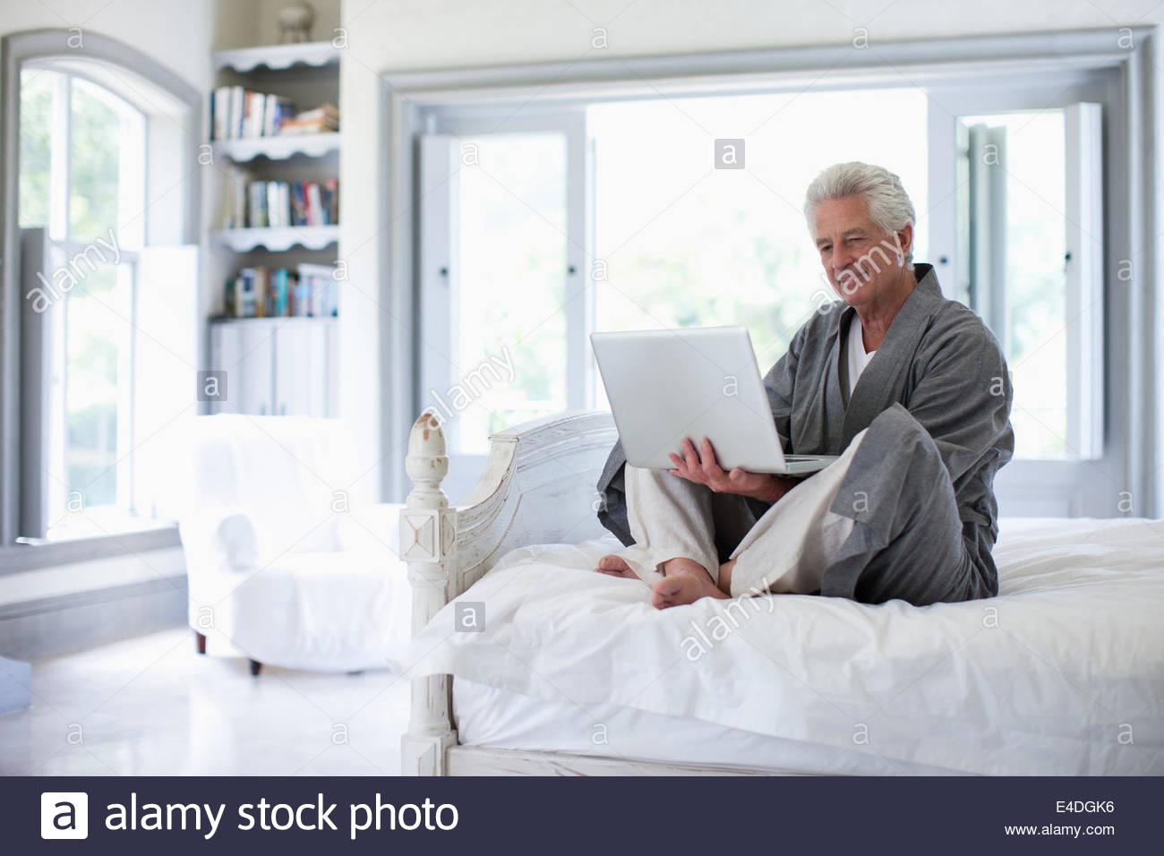 Senior uomo in accappatoio utilizzando computer portatile in camera da letto Immagini Stock
