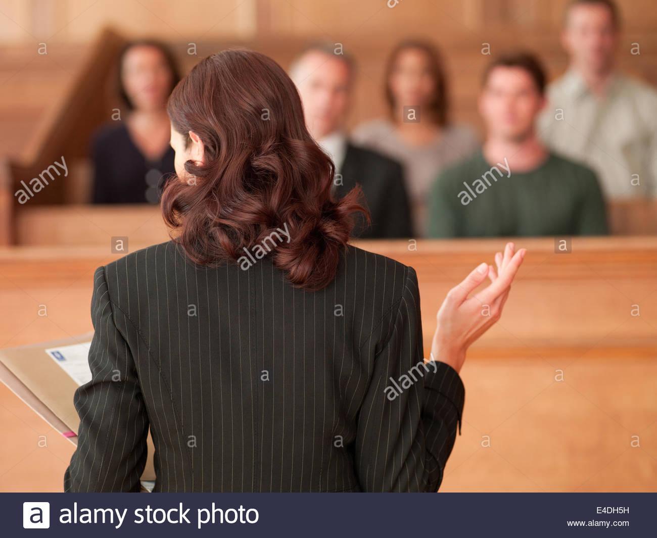Avvocato in possesso di documento e parlando alla giuria nelle aule di tribunale Immagini Stock