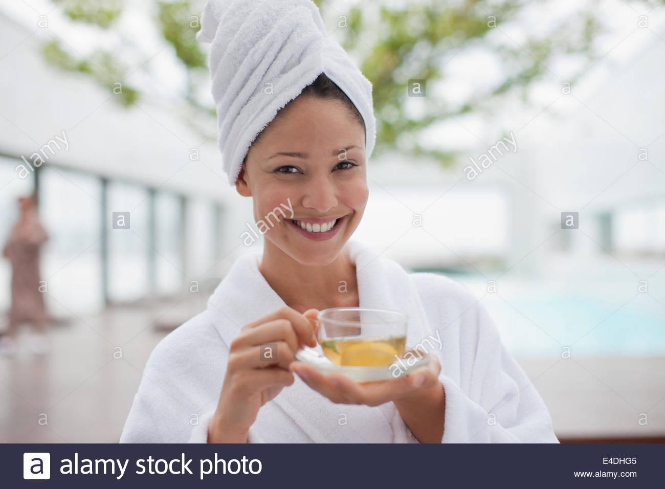 Donna con testa avvolto in asciugamano bere il tè Immagini Stock