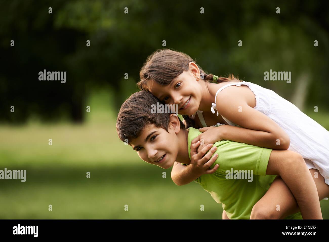 Persone in amore con felice bambina e ragazzo in esecuzione piggyback nel parco della città. Spazio di copia Immagini Stock