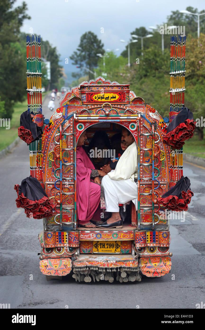 Il Pakistan, Islamabad, passeggeri a bordo di un minibus decorato, i mezzi di trasporto pubblico Immagini Stock