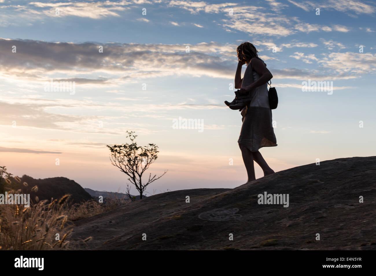 Silhouette di donna al telefono correre a piedi nudi attraverso colline remoto al crepuscolo azienda di scarpe in Immagini Stock