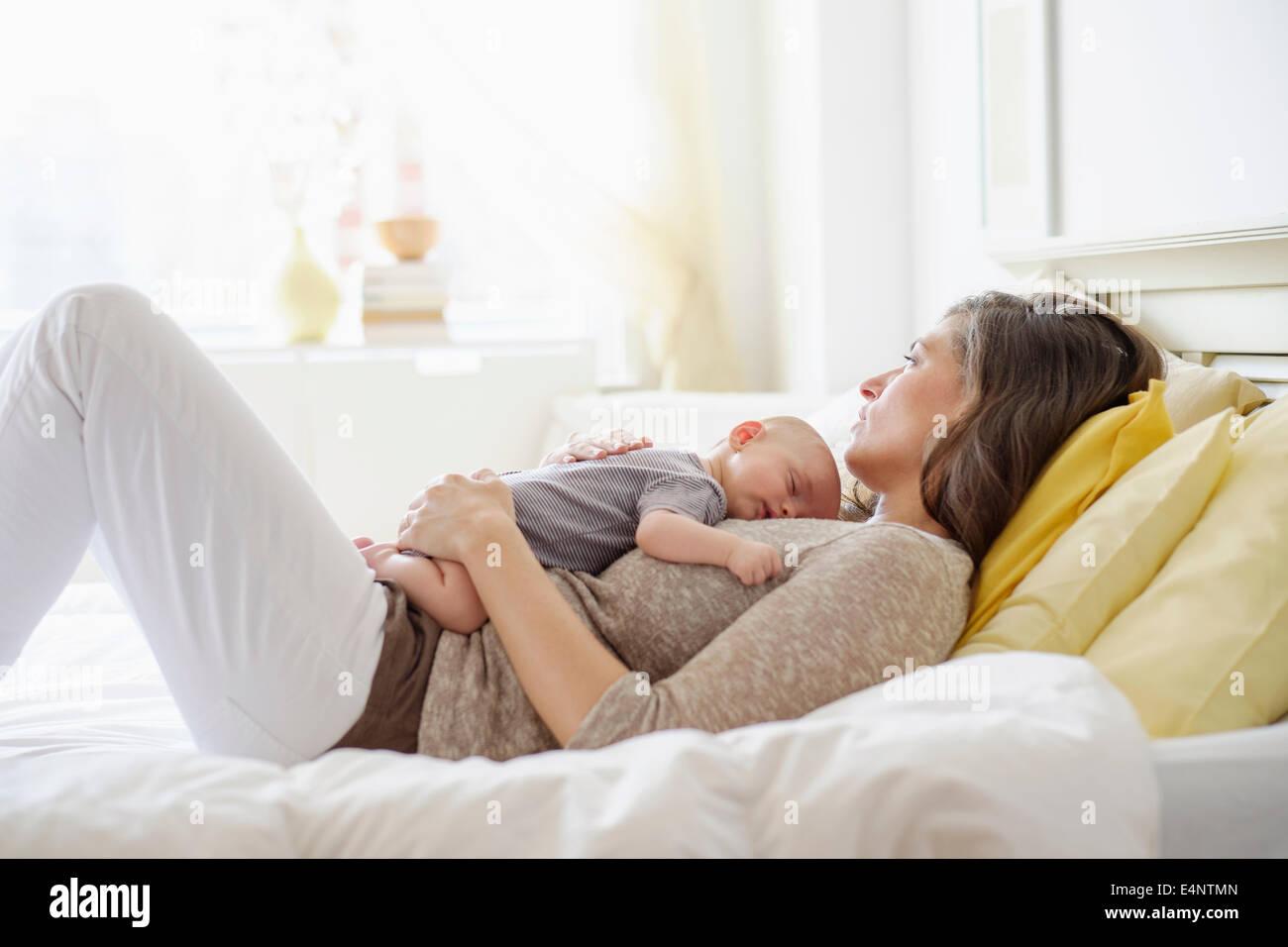 Madre giacente in letto con baby boy (2-5 mesi) Immagini Stock