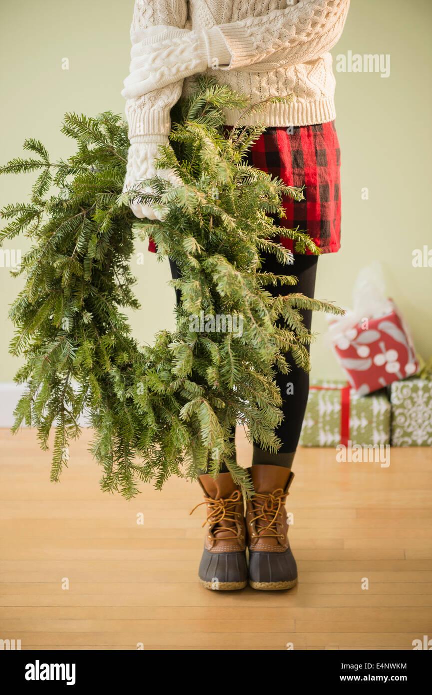 Sezione bassa di donna holding ghirlanda di Natale Immagini Stock