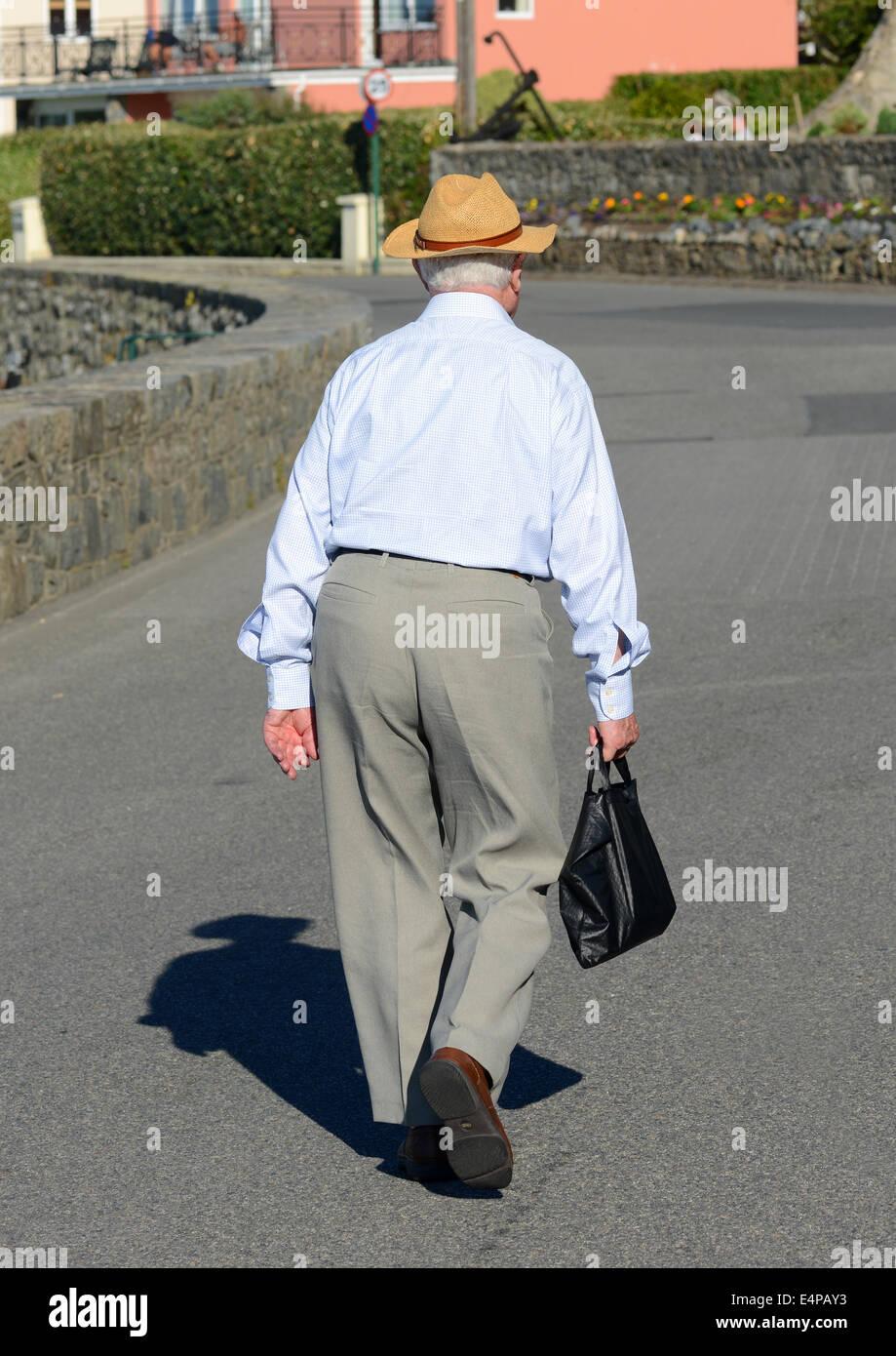 Un vecchio uomo che porta delle sue mogli borsetta Immagini Stock