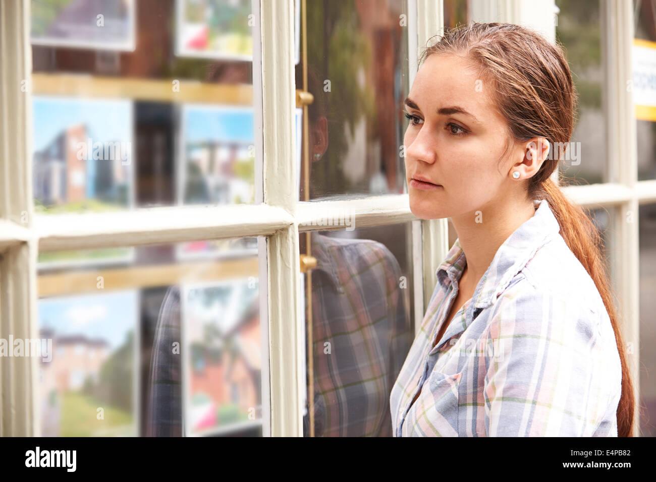 Deluso giovane donna guardando nella finestra degli Agenti Immobiliari Immagini Stock
