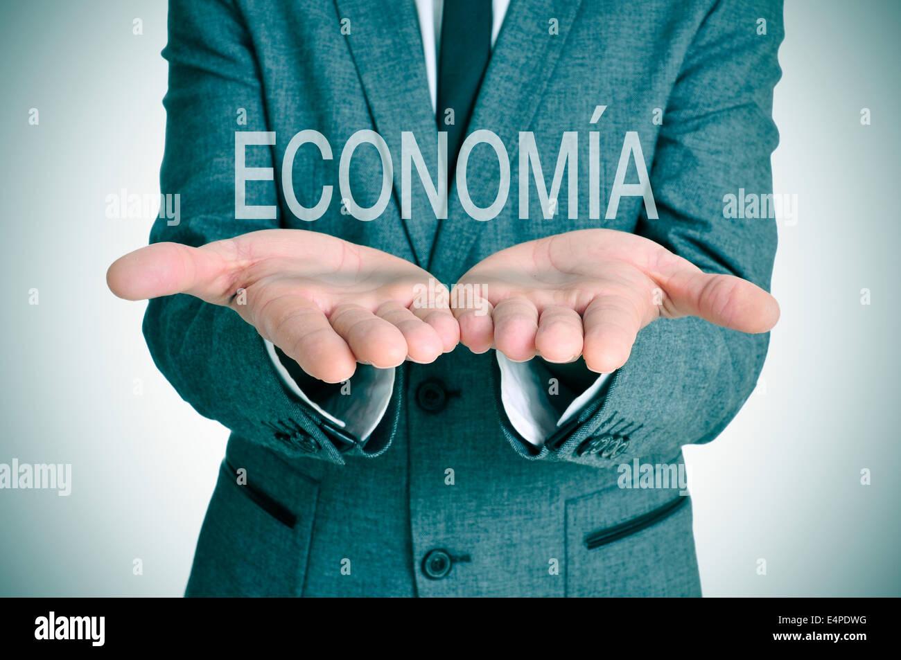 Un imprenditore con la parola economia, economia in spagnolo, nelle sue mani Immagini Stock