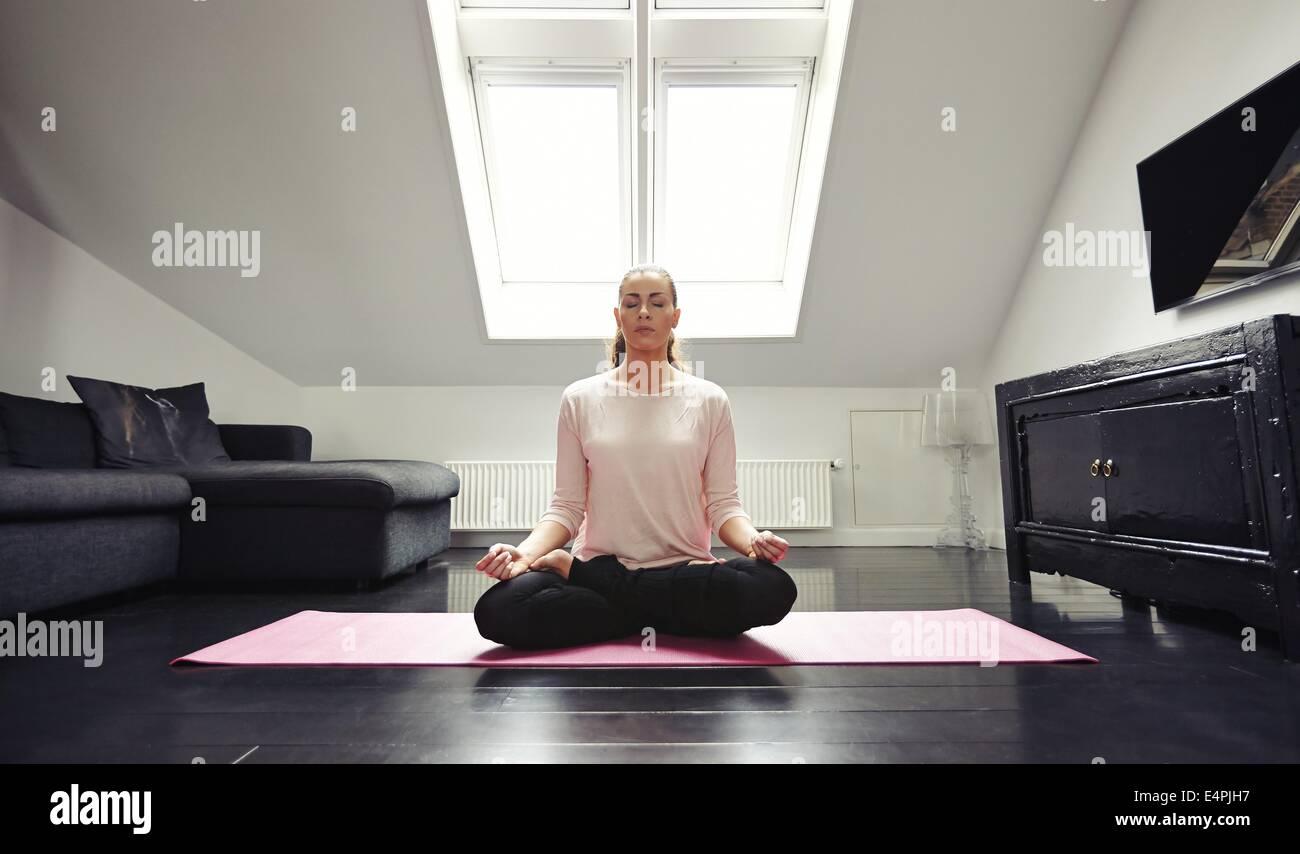 Ritratto di giovane donna meditando nella posizione del loto a casa. Caucasian modello femminile seduta con le gambe Immagini Stock