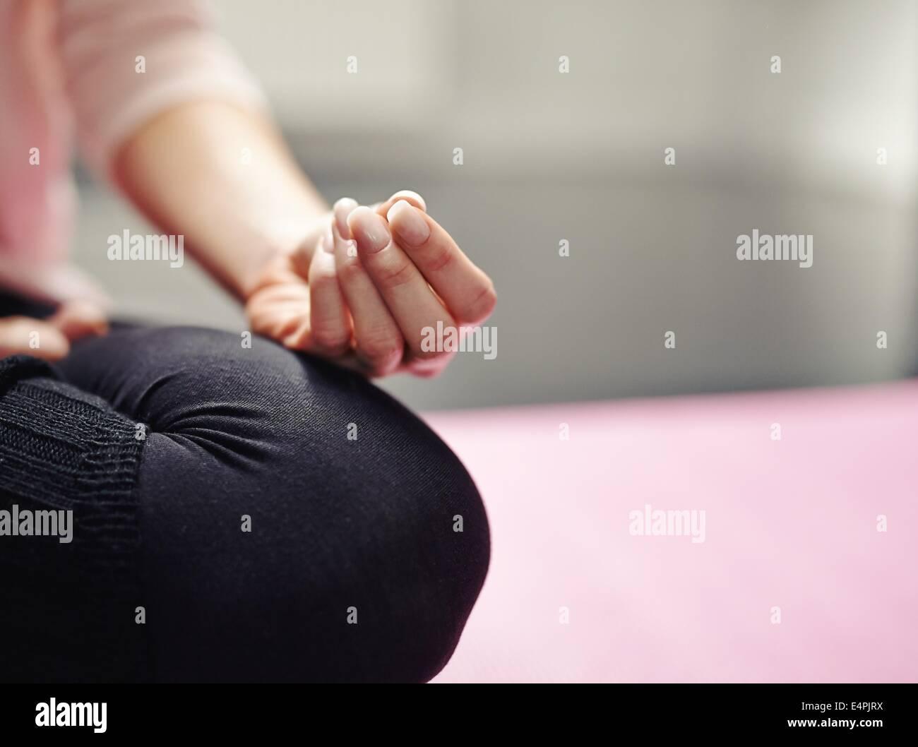 Sezione bassa di donna seduta con le gambe incrociate sul tappetino meditazione yoga in postura. Immagine ritagliata Immagini Stock