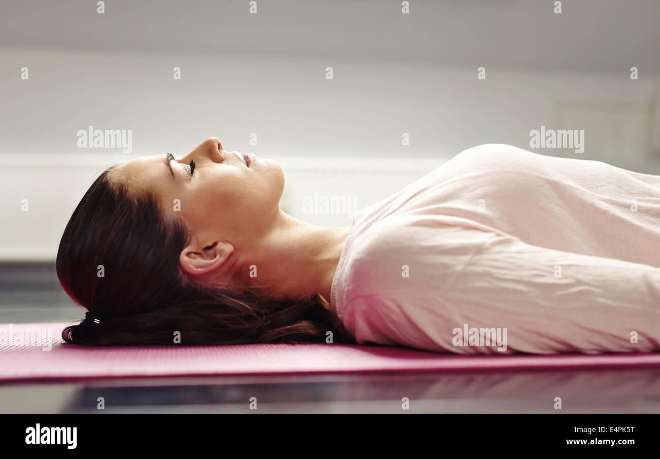 Chiudere l immagine della giovane donna sdraiata su un materassino yoga con gli occhi chiusi in meditazione. Immagini Stock