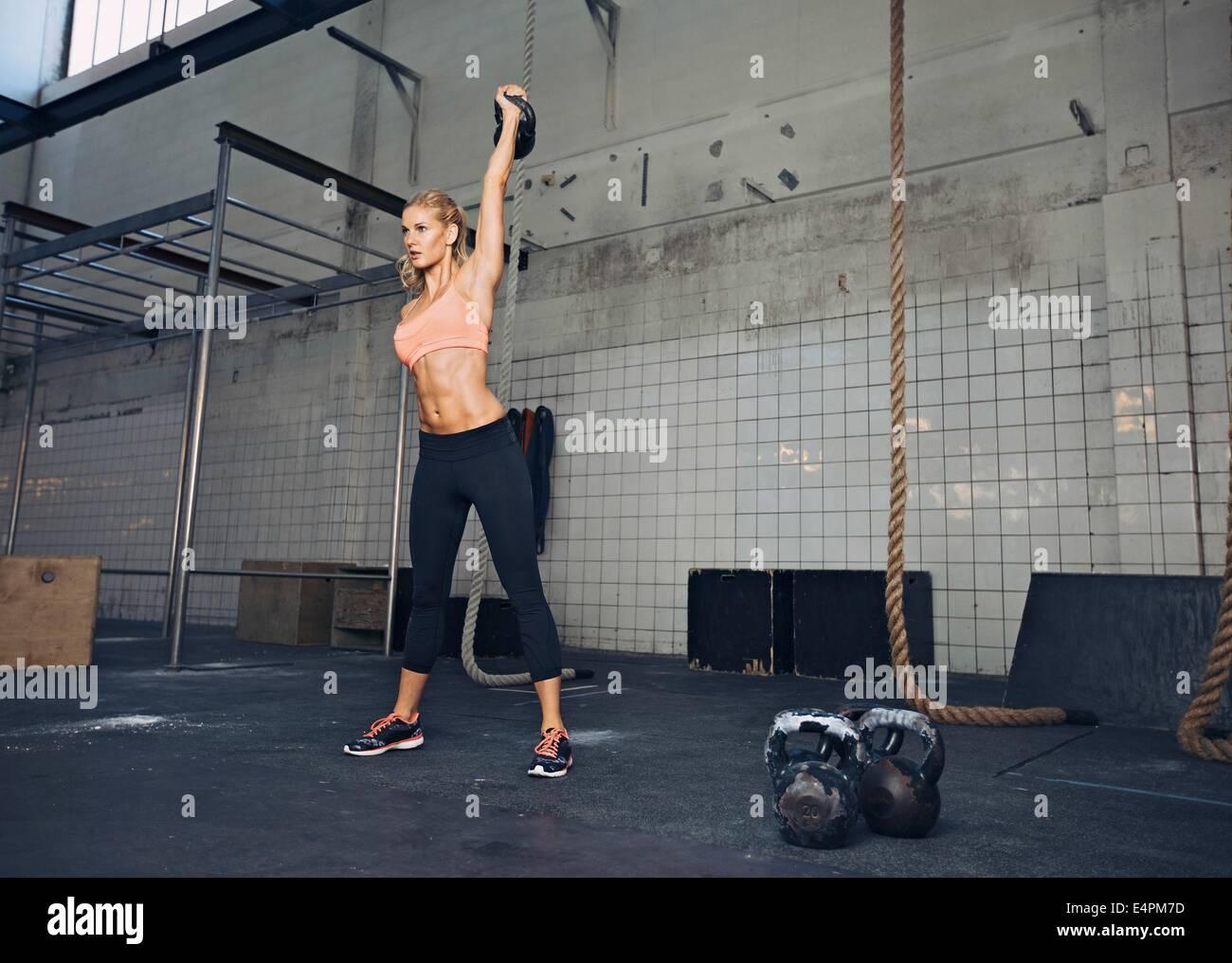 Giovane donna fitness sollevamento di un carico pesante bollitore bell in palestra. Caucasian atleta femminile lavora Immagini Stock