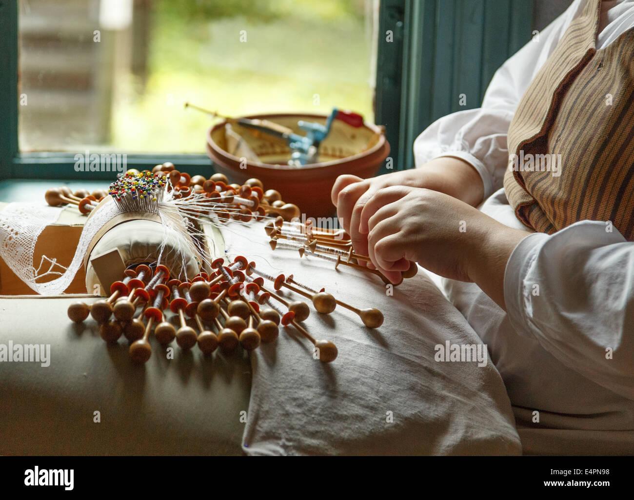 Il merletto a tombolo essendo prodotta con il metodo tradizionale a mano con rocche e un cuscino con i perni guida Immagini Stock