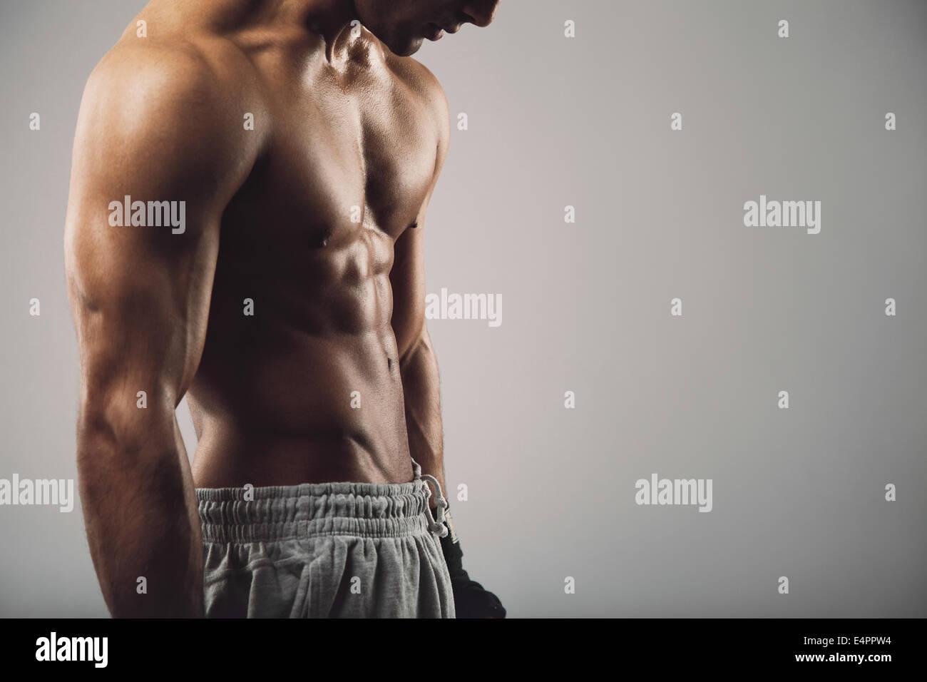 Immagine ritagliata del maschile giovane ragazzo su sfondo grigio con copia spazio. Allenamento fitness e tema. Immagini Stock