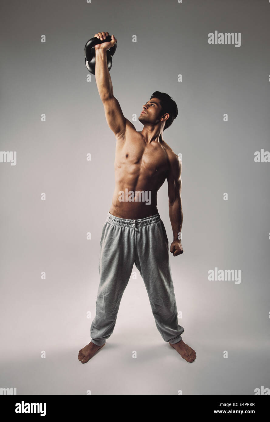 Bello e atletico giovane uomo di sollevare un kettlebell con una mano come un allenamento crossfit. Uomo muscolare Immagini Stock