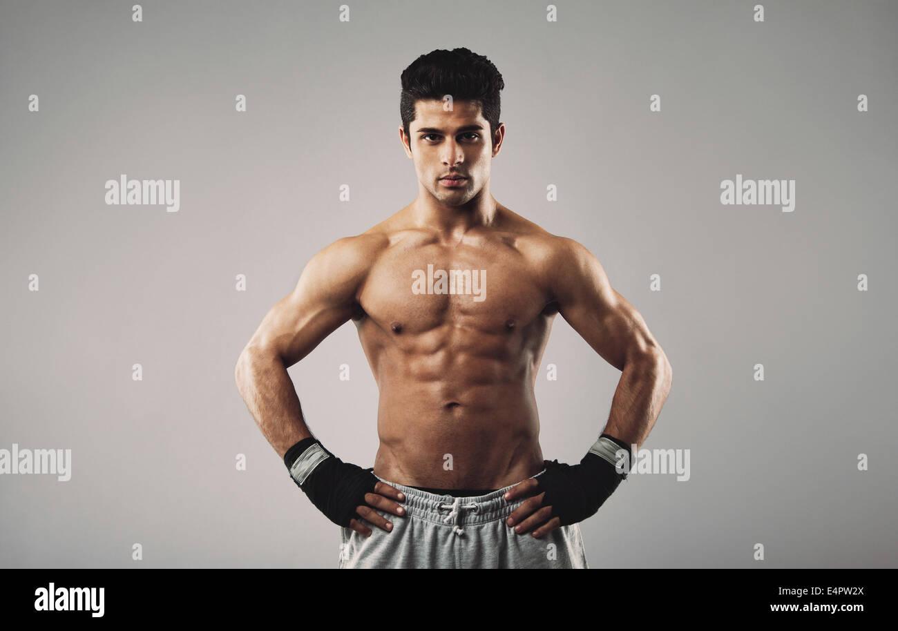Ritratto di giovane uomo muscolare in piedi con le mani sui fianchi contro uno sfondo grigio. Robusto giovane uomo Immagini Stock