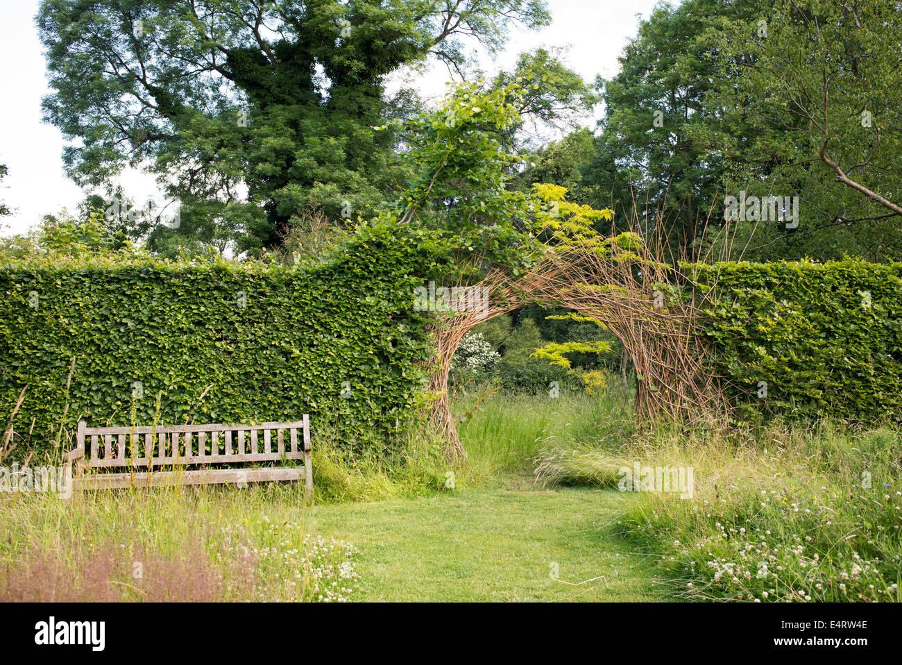 Willow Archway dividendo una siepe su giardino percorso ad RHS Harlow Carr. Harrogate, Inghilterra Immagini Stock