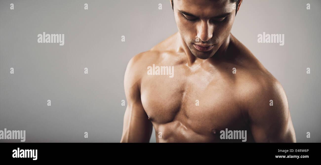 Ritratto di montare shirtless maschile uomo che guarda verso il basso. Ampia panoramica del prodotto con copia spazio. Immagini Stock