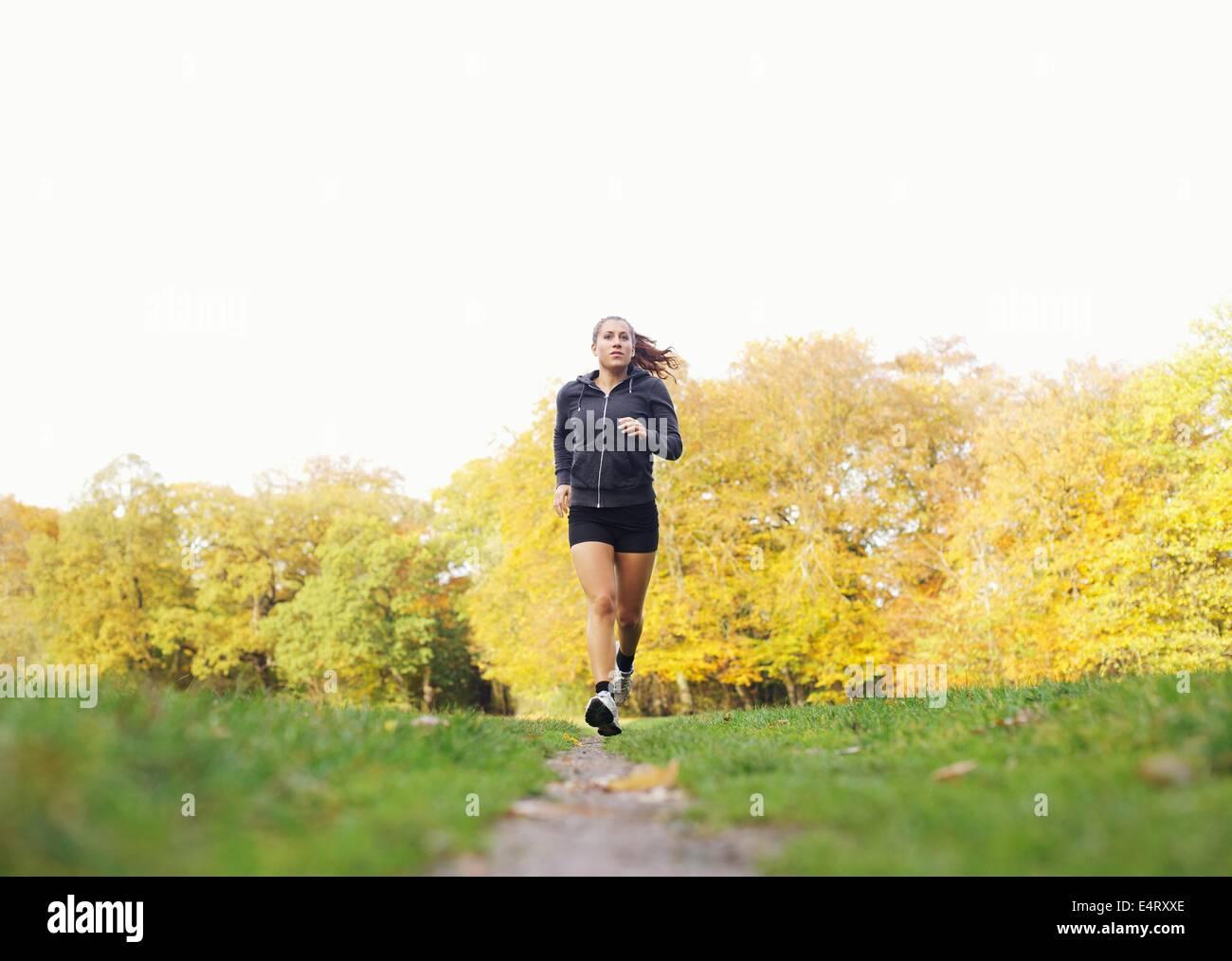 Montare e sano giovane donna in esecuzione al di fuori nel parco. Modello di fitness in capi di abbigliamento sportivi Immagini Stock